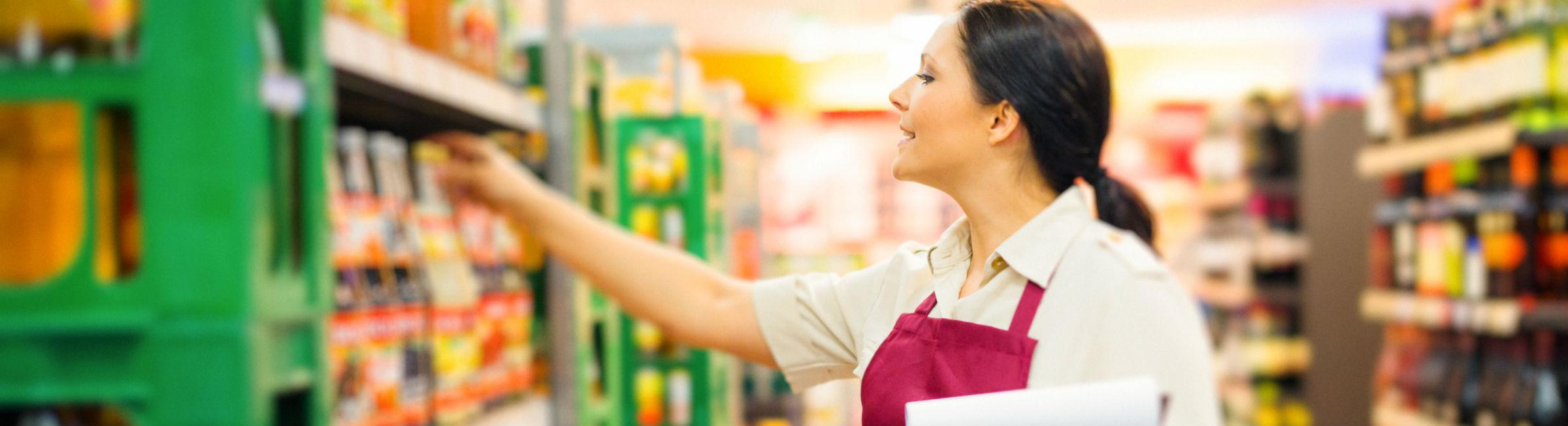Un femme fait de la mise en rayon dans un supermarché