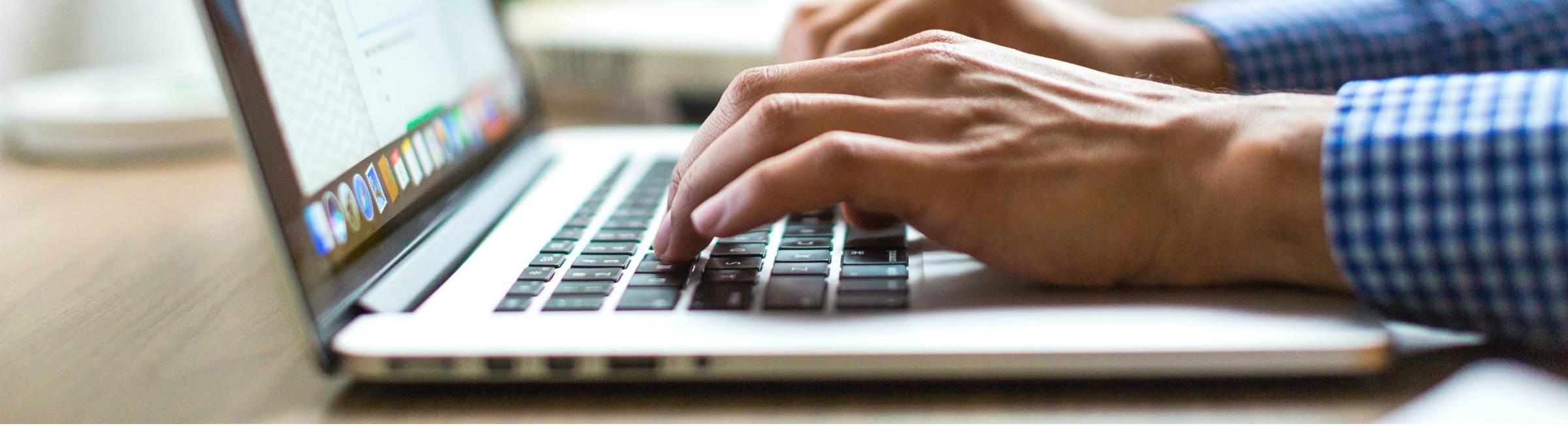 Un homme écrit sur son ordinateur portable