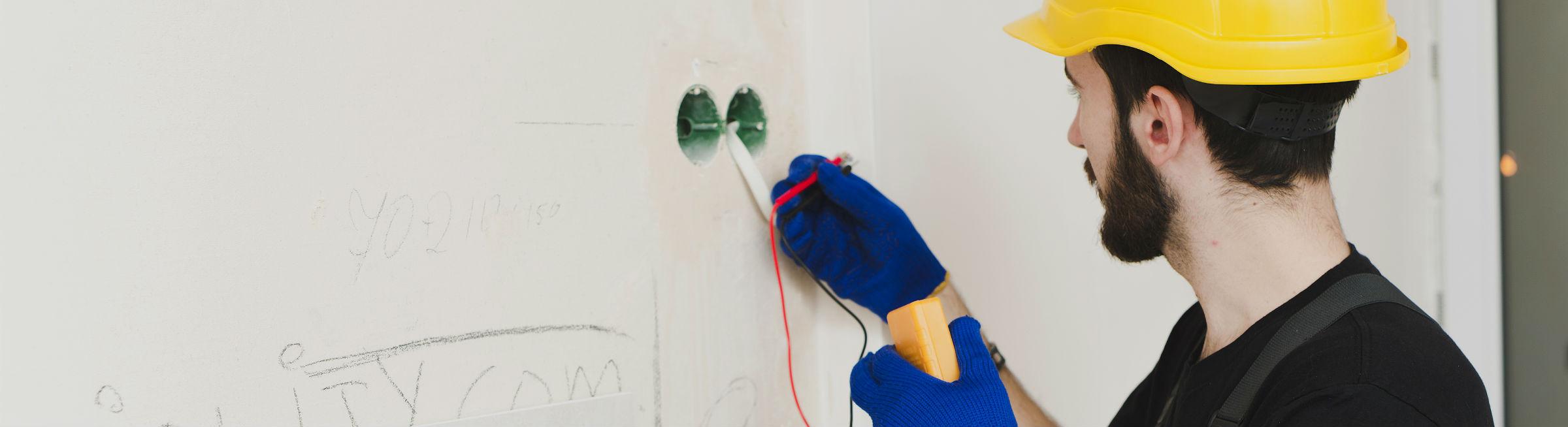 Un électricien effectue des branchements électriques
