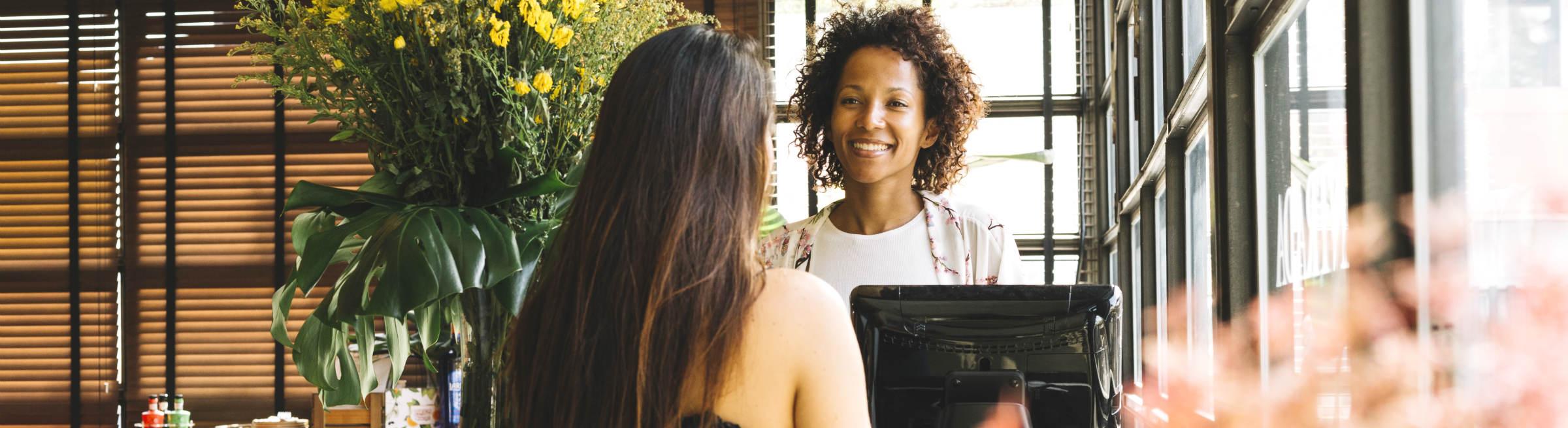 Une employé libre-service accueille une cliente